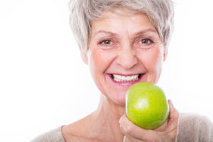 smiling senior woman holding a green apple