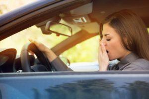 woman tired yawning in car