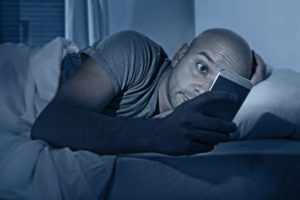 person on their cellphone laying in bed